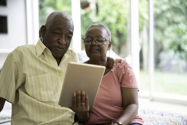 African senior couple using digital tablet